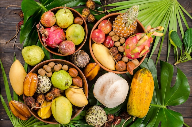 Assortiment de fruits tropicaux thaïlandais sur un fond rustique en bois foncé.