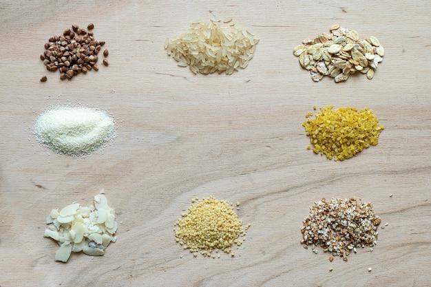 Assortiment de graines de bouillie de céréales sur un fond en bois: sarrasin, riz, semoule, blé, couscous, flocons d'avoine