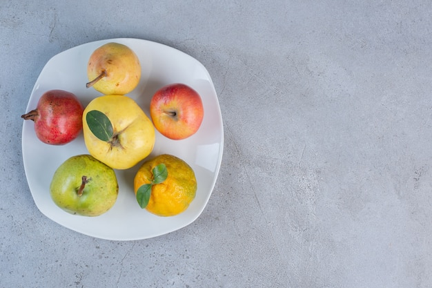 Assortiment de grenade, poires, mandarine, coing et pomme sur un plateau sur fond de marbre.