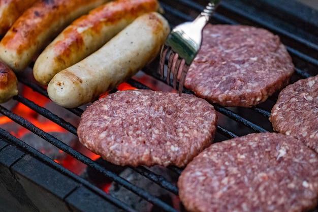 Assortiment de grillades à base de viande de poulet et de porc, saucisses rôties sur une grille de barbecue cuites pour le dîner d'été en famille.