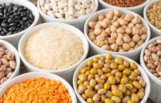 Un assortiment de haricots et de céréales sur des bols blancs.
