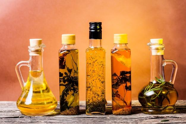 Assortiment d'huiles épicées aux herbes et épices dans différentes bouteilles