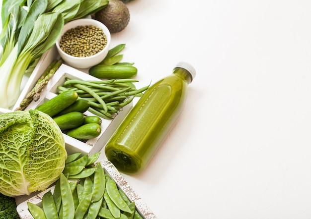 Assortiment de légumes biologiques crus aux tons verts avocat, chou, chou-fleur et concombre avec haricots parés et mungo et bouteille de smoothie.