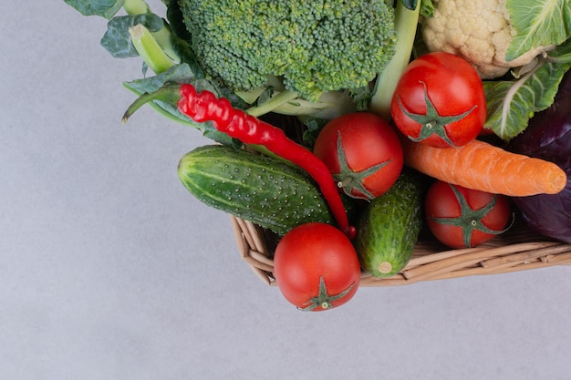 Assortiment de légumes biologiques dans un panier en bois.