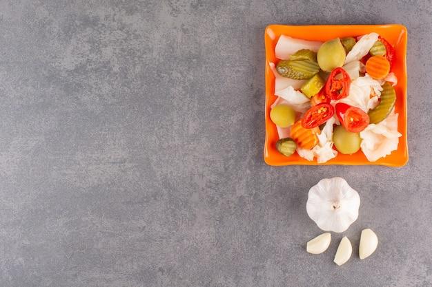 Assortiment de légumes cornichons dans un bol placé sur une table en pierre.