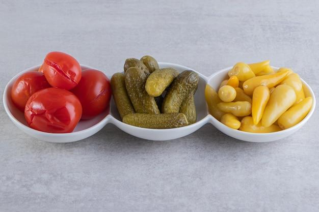 Assortiment de légumes cornichons placés dans trois bols blancs.