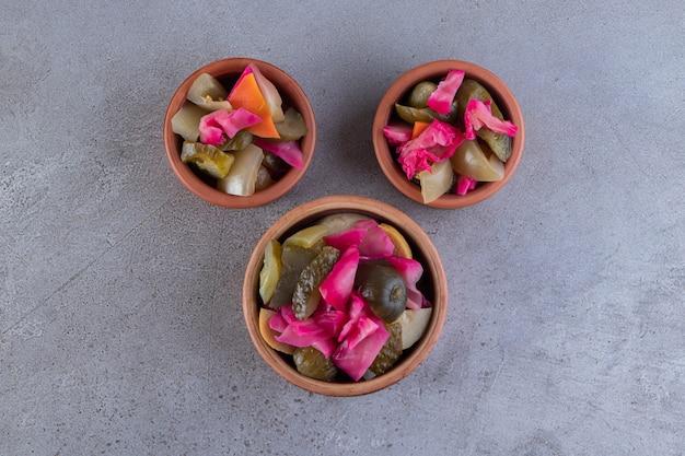 Assortiment de légumes cornichons placés sur une surface en pierre.