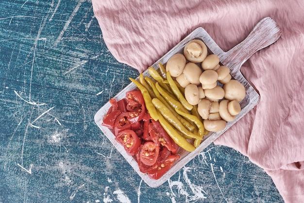 Assortiment de légumes marinés sur plaque blanche avec nappe.