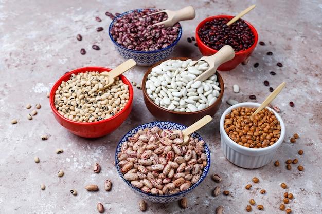 Assortiment de légumineuses et de haricots dans différents bols sur fond de pierre clair. vue de dessus. nourriture protéinée végétalienne saine.