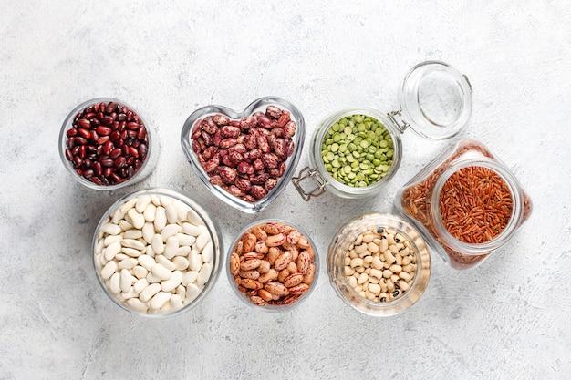 Assortiment de légumineuses et de haricots dans différents bols sur fond de pierre claire. vue de dessus. aliments protéinés végétaliens sains.