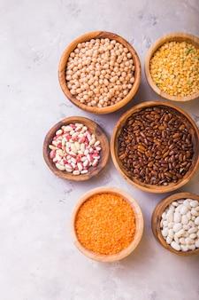 Assortiment de légumineuses, lentilles, pois chiches et haricots dans différents bols sur tableau blanc.