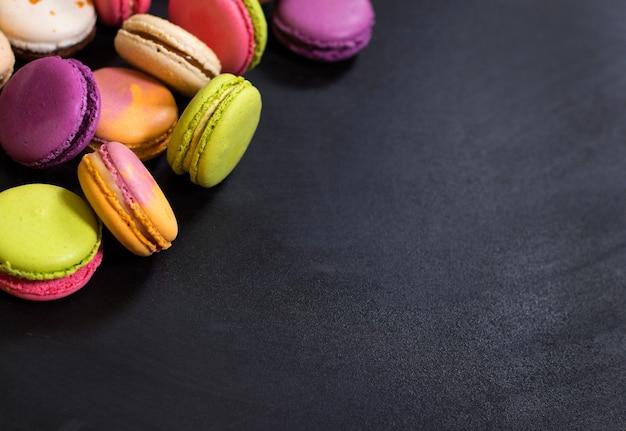 Assortiment de macarons biscuits français colorés sur fond noir.