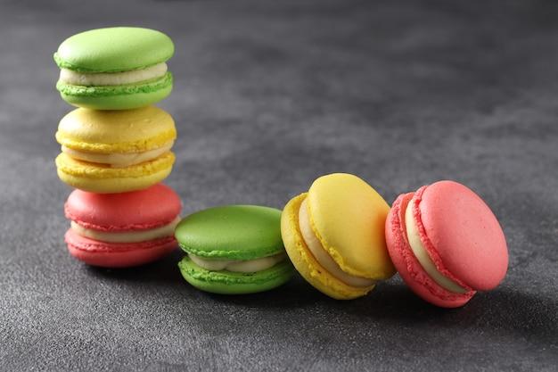 Assortiment de macarons français colorés sur fond gris foncé. fermer.