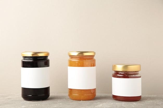 Assortiment de maquettes de pots de confiture. pots avec étiquette vierge sur gris. vue de dessus