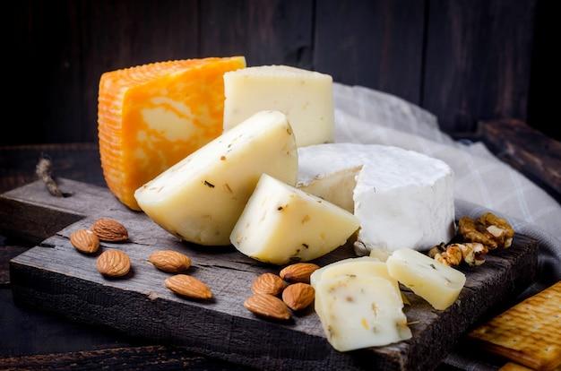 Assortiment de morceaux de fromage faits maison avec du miel, des fruits, des biscuits et des noix sur la table. produits laitiers frais, aliments biologiques sains. délicieux apéritif.