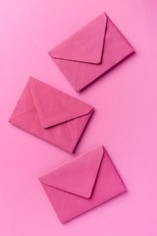 Assortiment de natures mortes monochromes avec enveloppes roses