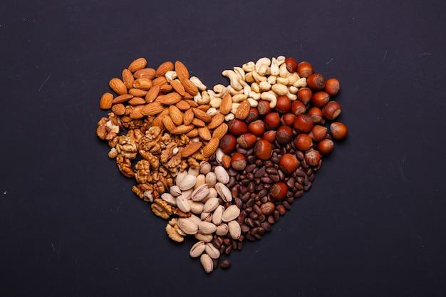 Assortiment de noix sur une ardoise noire - collation santé. coeur de noix