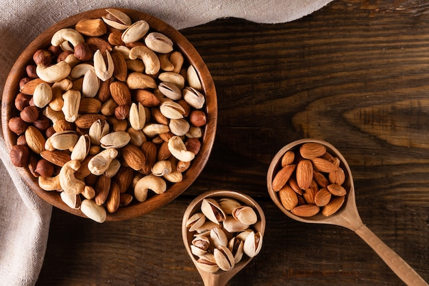 Assortiment de noix dans un bol en bois sur une table en bois sombre. noix de cajou, noisettes, amandes et pistaches.