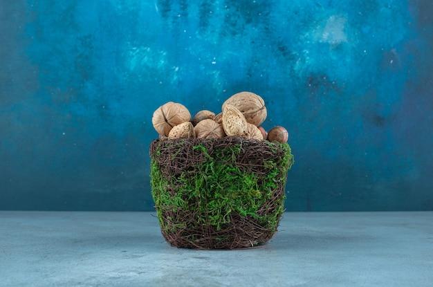 Assortiment de noix dans un bol fantaisie sur marbre.