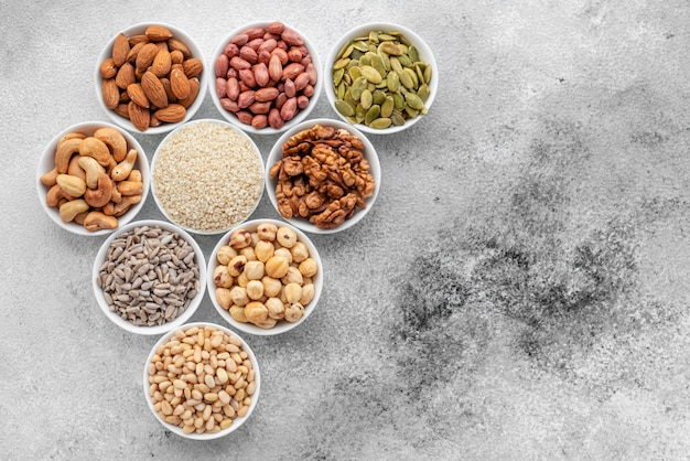 Assortiment de noix dans des soucoupes blanches sur un fond de béton. fond de mélange alimentaire, vue de dessus, espace copie, bannière