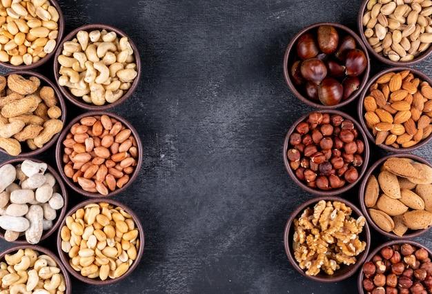 Assortiment de noix et fruits secs à plat dans des mini bols différents avec pacanes, pistaches, amandes, arachides