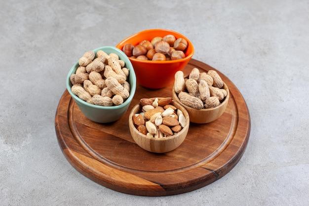 Un assortiment de noix soigneusement empilées dans quatre bols sur un plateau en bois sur une surface en marbre