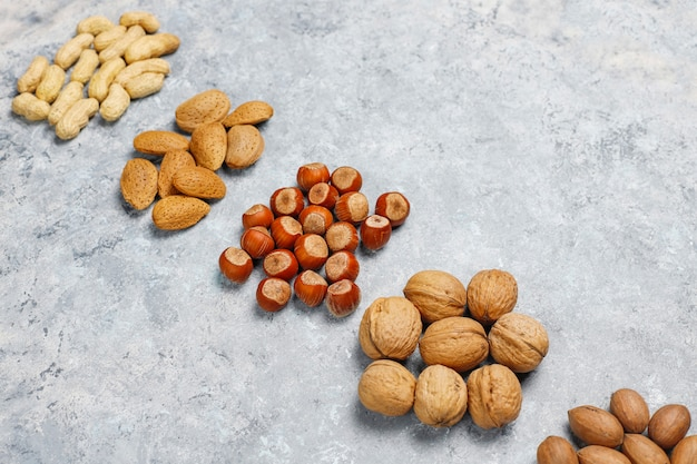 Assortiment de noix sur la surface en béton. noisettes, noix, noix de pécan, arachide, amandes, vue de dessus
