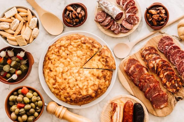 Assortiment de nourriture et cuillères autour de la tarte