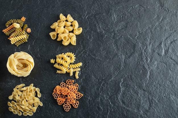 Assortiment de pâtes crues sur fond sombre. photo de haute qualité