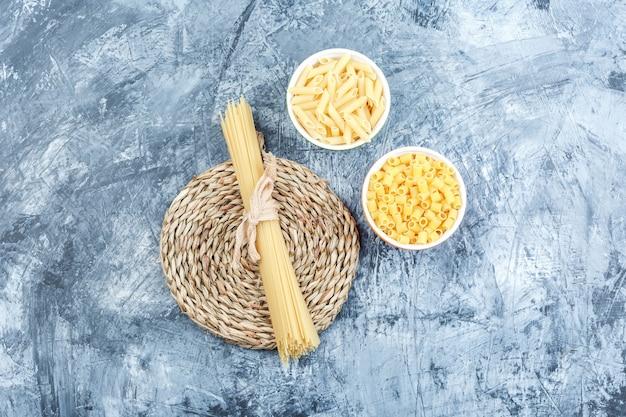 Un assortiment de pâtes dans des bols sur fond de plâtre et d'osier gris, vue du dessus.