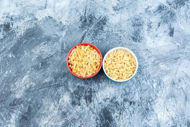 Assortiment de pâtes dans des bols sur un fond de plâtre sale. pose à plat.