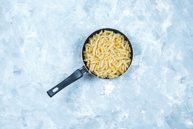 Assortiment de pâtes dans une casserole vue de dessus sur un fond gris grungy