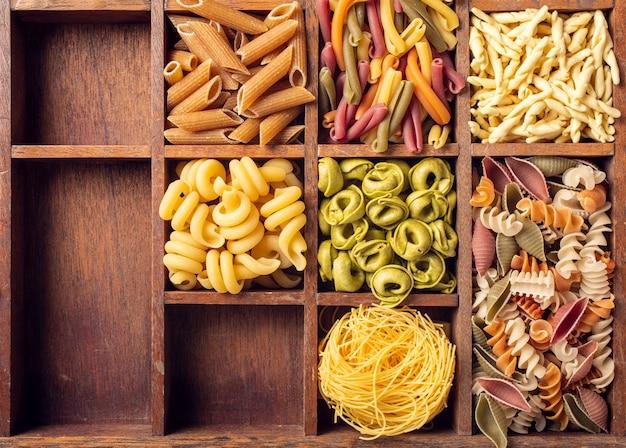 Assortiment de pâtes italiennes colorées dans une boîte en bois