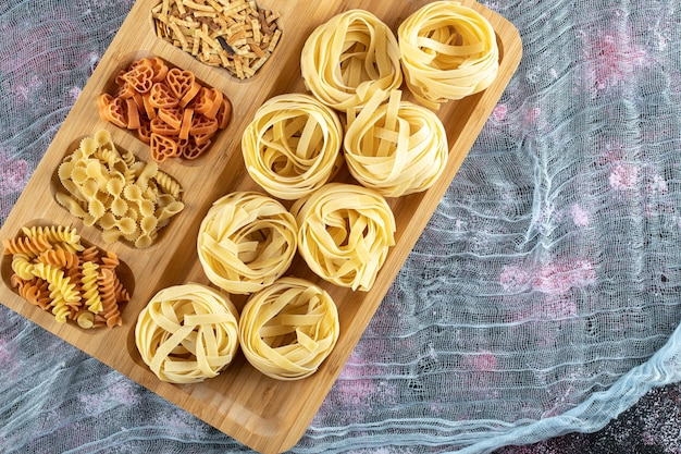 Assortiment de pâtes non cuites sur plaque de bois. photo de haute qualité