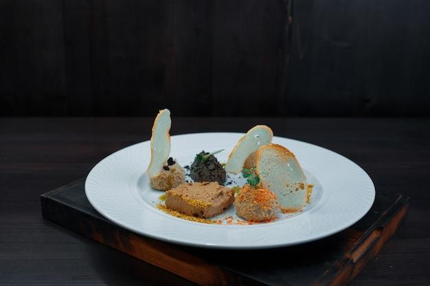 Assortiment de pâtes de viande sur une assiette blanche dans un restaurant. apéritif savoureux original.