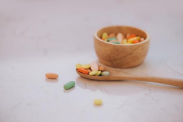 Assortiment de pilules, comprimés et capsules de médecine pharmaceutique sur bol en bois