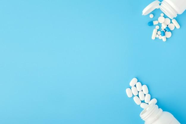 Assortiment de pilules, comprimés et capsules de médecine pharmaceutique et bouteille sur fond bleu. copiez l'espace pour le texte