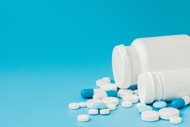 Assortiment de pilules, comprimés et capsules de médecine pharmaceutique et bouteille sur mur bleu. copiez l'espace pour le texte