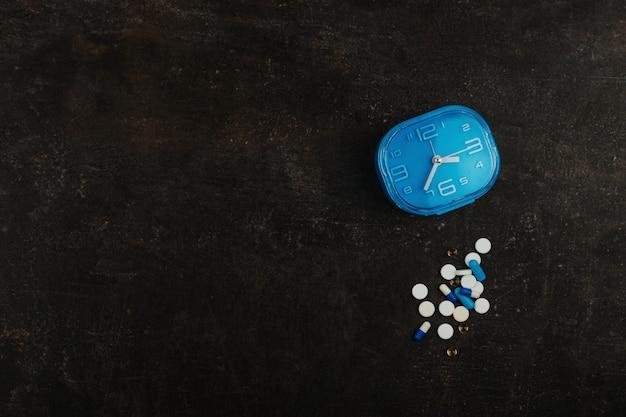 Assortiment de pilules et horloge bleue sur une table sombre. concept de médicament santé