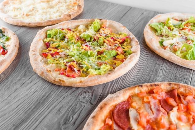 Assortiment de pizza avec viande, salami, prosciutto, tomates, fromage dorblu, mozzarella, parmesan, salade, épinards, poisson rouge sur des planches de bois. pizza aux quatre fromages, césar, vue de dessus.