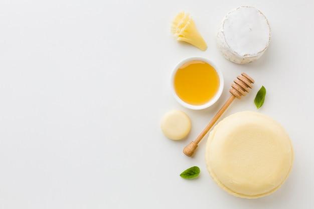 Assortiment plat de fromages ronds et de miel avec espace de copie