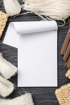 Assortiment plat de nouilles non cuites avec un cahier vierge