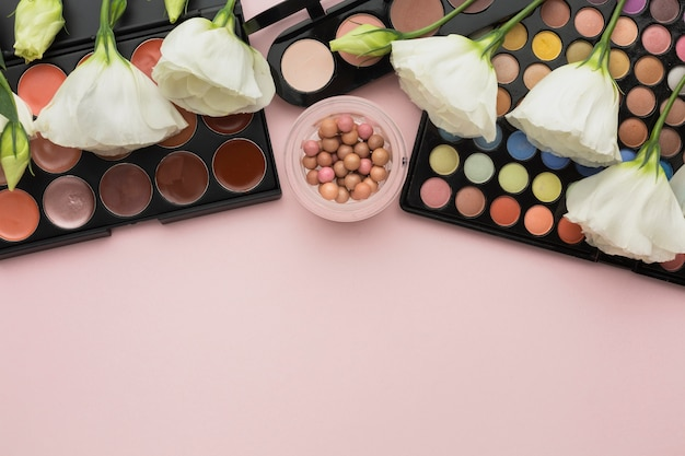 Assortiment à plat avec des palettes de maquillage et des fleurs