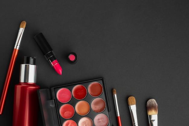 Assortiment à plat avec produits de maquillage sur fond noir