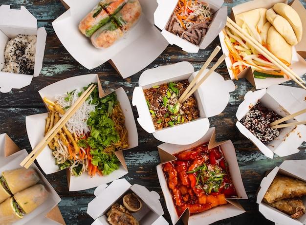 Assortiment de plats chinois dans des boîtes de livraison en papier : poulet aigre-doux, dim sum, rouleaux de printemps, nouilles, salade, riz, petits pains vapeur, trempettes. concept de restaurant asiatique à emporter, vue de dessus