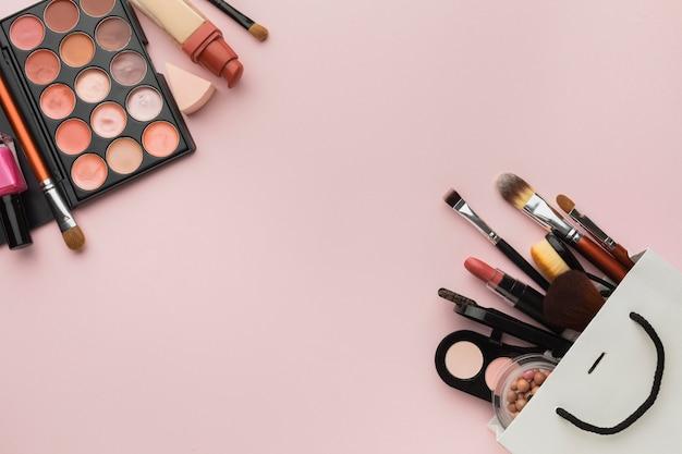 Assortiment de plats à plat avec cadre de maquillage sur fond rose