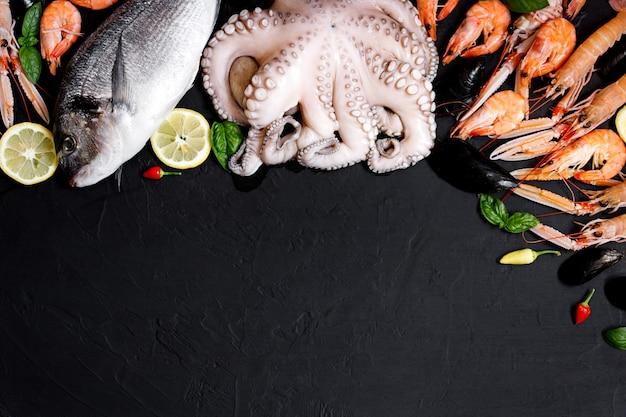 Assortiment de poissons et fruits de mer sains sur fond noir. vue de dessus. fruits de mer sur fond rustique noir.