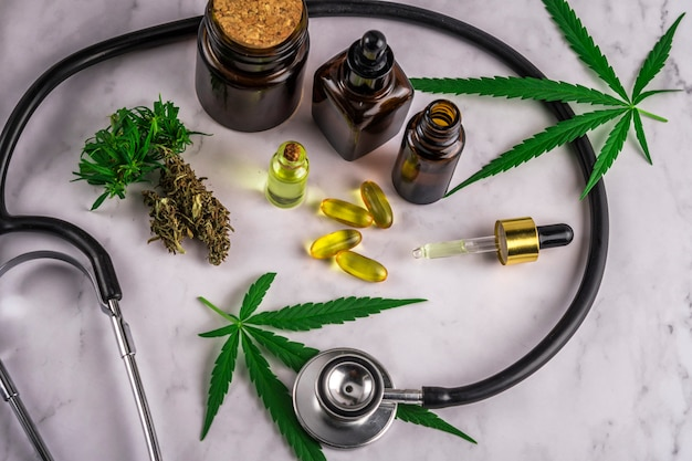 Assortiment de produits à base de cannabis, de pilules et d'huile de cdb sur une feuille d'ordonnance médicale