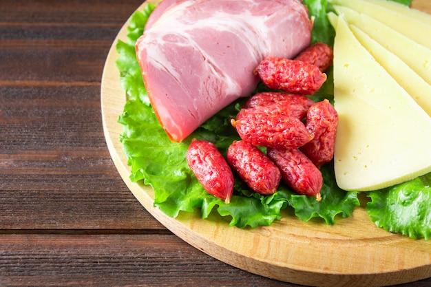 Assortiment de produits à base de viande comprenant du jambon et des saucisses. fromage
