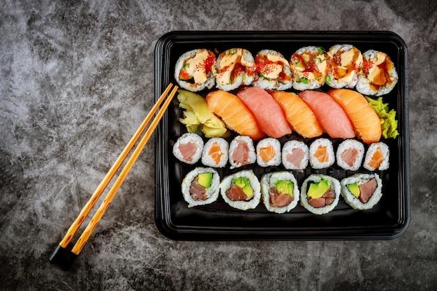 Assortiment de rouleaux de sushi sur un plateau noir. nourriture japonaise. vue de dessus.